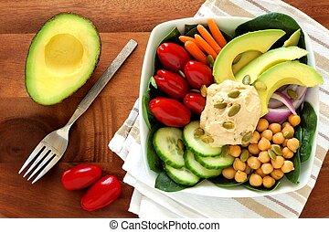 Zdravá avokádová mísa s humusem a čerstvým zeleninou, nad dřevěným stolem