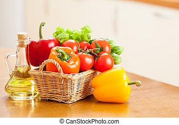 Zdravá zelenina v koši a láhev s olejem na kuchyňský stole