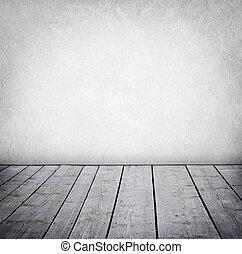 Zeď a dřevěná podlaha.