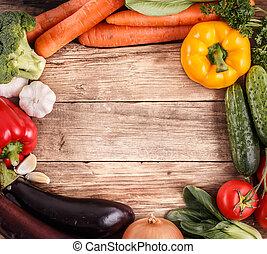 Zelenina na dřevěném pozadí s prostorem. Organické jídlo.
